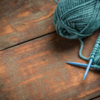 Woollen thread and knitting needle on wooden background